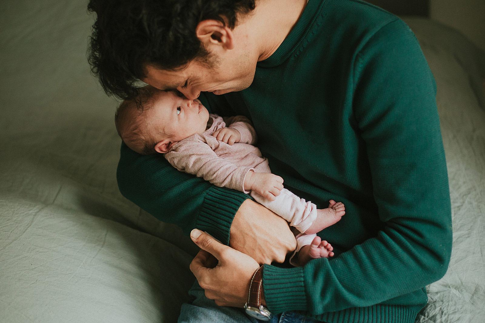papa houdt baby in arm tijdens newborn shoot utrecht